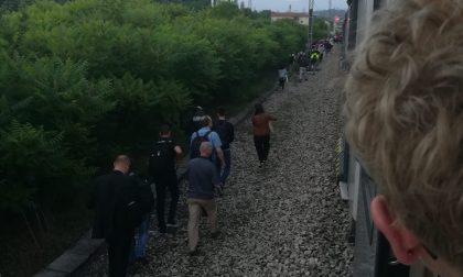 Treno fermo i pendolari si incamminano lungo i binari